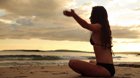 Peaceful brunette meditating on the sand at sunset Footage