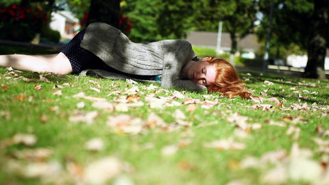 Peaceful napping redhead lying on green lawn Footage