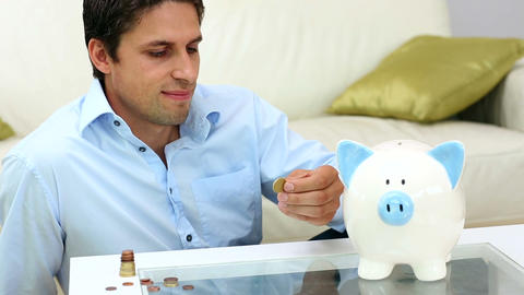 Cute young man putting money into a piggy bank Footage