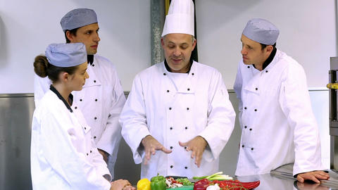 Head chef showing his trainees how to slice vegeta Footage