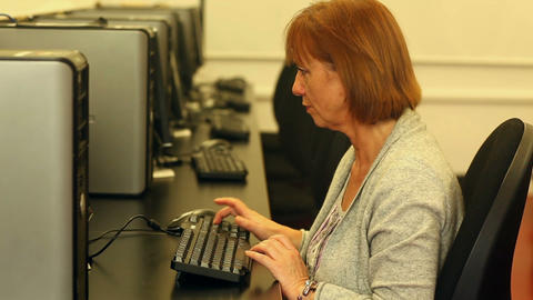 Mature student working with a computer sitting in computer room Footage