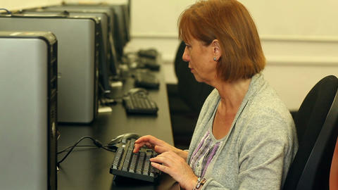 Mature student working with a computer sitting in computer class Live Action