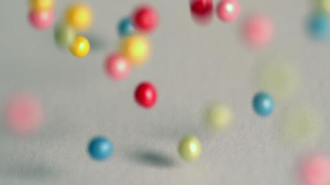 Sugar balls falling onto grey surface Footage