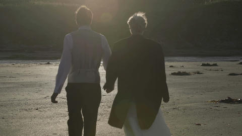 Smiling newlyweds walking together on the beach Footage