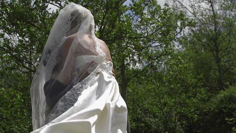 Groom picking up his pretty new wife in a park Live Action