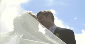 Bride and groom kissing each other outside on a su Footage