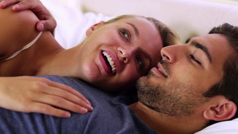 Cute couple chatting and cuddling in bed Footage