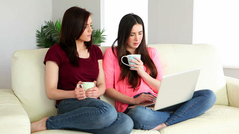 Brunette using laptop and chatting to her friend o Footage