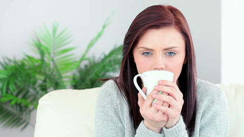 Pretty brunette drinking mug of coffee on the couc Footage