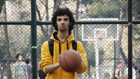 Young man play basketball ball turn on finger streetball sport game Footage