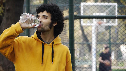 Young man play basketball streetball drink water sport game Stock Video Footage