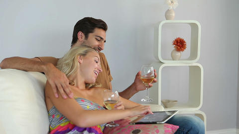 Smiling couple lying on couch using tablet pc drin Footage
