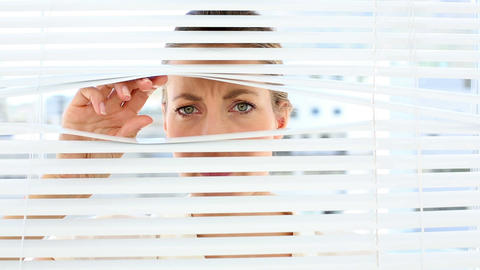 Stern businesswoman peeking through the blinds Footage