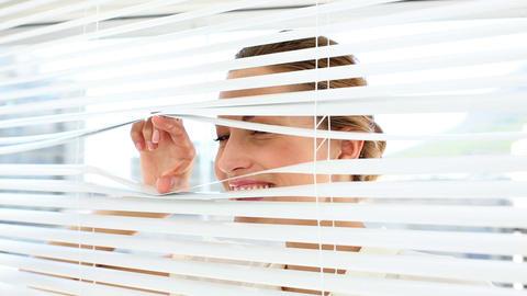 Shocked businesswoman peeking through the blinds Footage