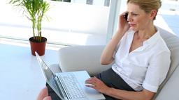 Businesswoman sitting on sofa using laptop talking Footage