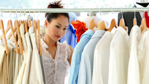 Fashion designer looking through her clothing rail Footage