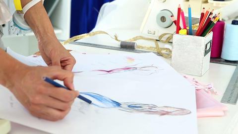 Fashion designer sketching a blue dress design Live Action