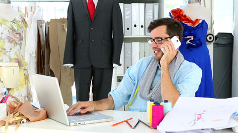 Designer talking on the phone and using the laptop Footage