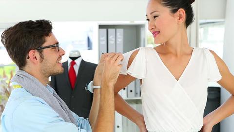 Designer adjusting sleeve of dress on model and sm Footage