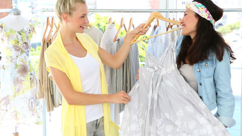 Friends admiring a dress and smiling at camera Footage