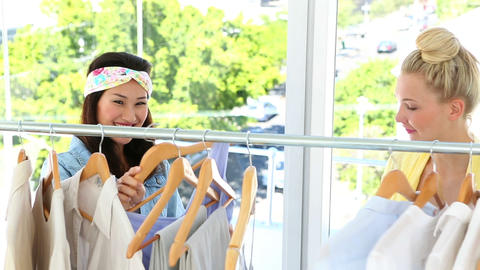 Pretty friends looking through clothing rail together Footage