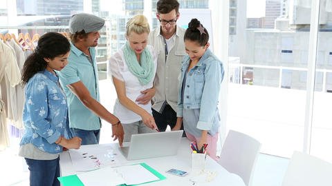Fashion team brainstorming together using laptop giving thumbs up to camera Footage