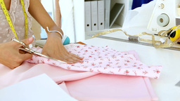 Designer cutting pink cloth with scissors Footage