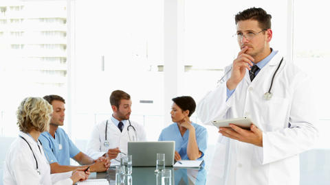 Thoughtful doctor using tablet with staff talking behind him Footage