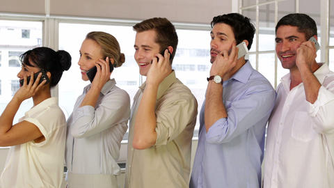 Businesspeople phoning while standing in a row Footage