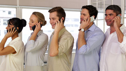 Businesspeople phoning while standing in a row Stock Video Footage