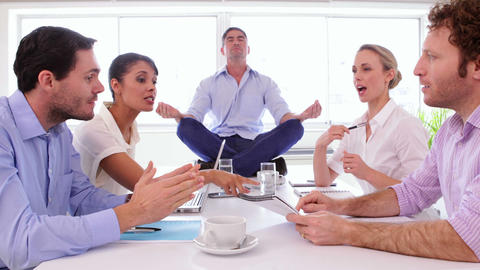 Businessman meditating while his colleagues are arguing Stock Video Footage