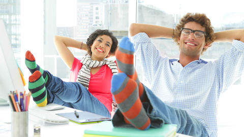 Two colleagues reclining on their swivel chair Stock Video Footage