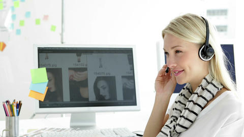 Cute blonde creative designer phoning with headset Stock Video Footage