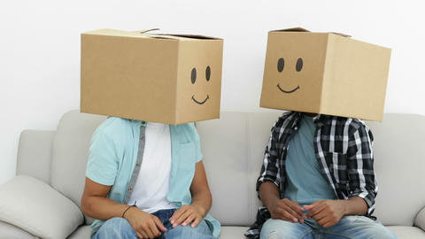 Silly employees with boxes on their heads giving thumbs up Stock Video Footage