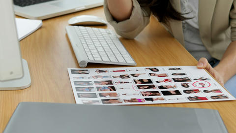 Photo editor circling head shots Stock Video Footage