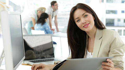 Woman working at her desk looking at folder Stock Video Footage