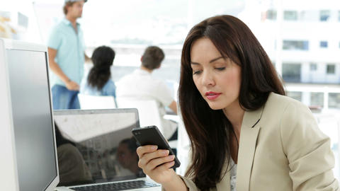 Woman working at her desk texting on the phone Stock Video Footage