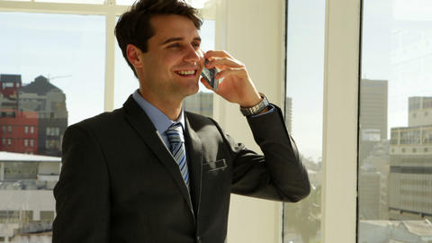 Businessman looking out his window talking on the phone Stock Video Footage