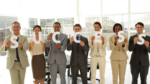 Business team holding letters spelling success Stock Video Footage
