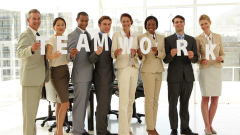 Happy business people holding letters spelling teamwork Stock Video Footage