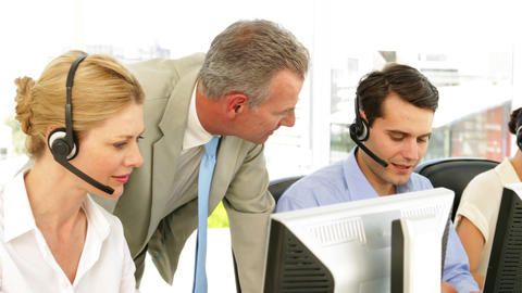 Manager checking on call centre employees Stock Video Footage