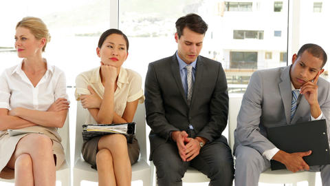 Business people waiting for an interview in a row Stock Video Footage