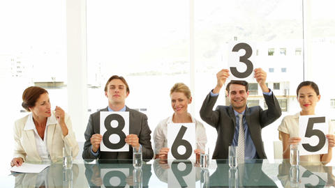 Interview panel holding up scores and smiling Stock Video Footage