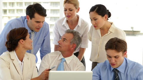 Smiling business team working in front of laptop Stock Video Footage