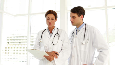 Doctors speaking about a file Stock Video Footage