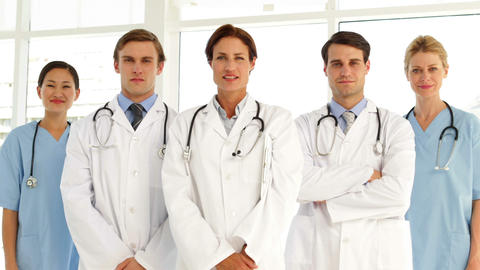 Confident medical team looking at camera and giving... Stock Video Footage