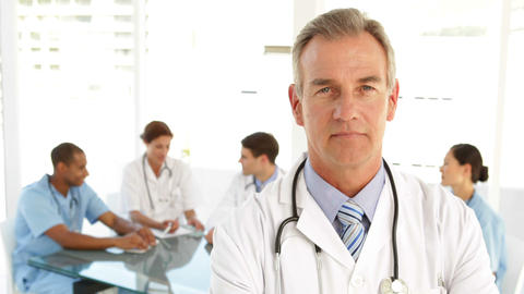 Doctor looking at camera and his staff behind him Stock Video Footage