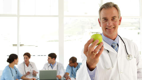 Mature doctor looking at camera holding an apple Stock Video Footage