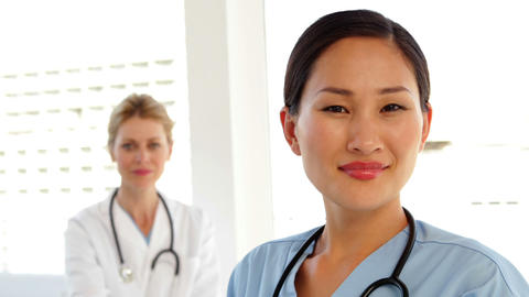 Smiling surgeon with doctor behind her Stock Video Footage