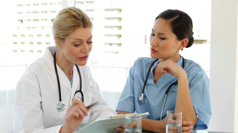 Doctor and nurse going over a file Stock Video Footage
